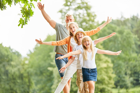 Sporty family and children balance with outstretched arms Фото со стока