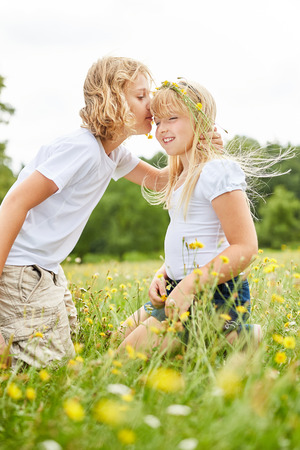 Brother lovingly kisses his sister on the forehead in a summer meadow Stockfoto