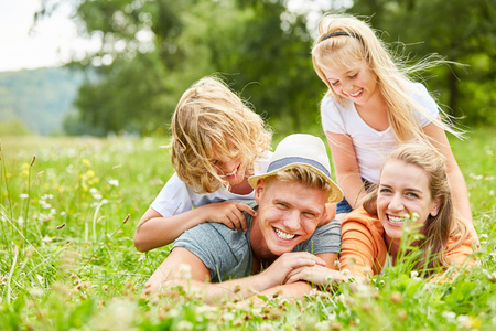 Children have fun playing with their parents on a summer meadow