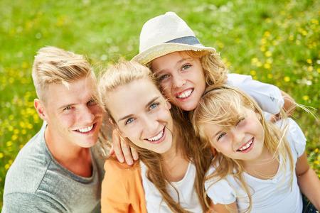 Famiglia felice e due bambini in giardino d'estate