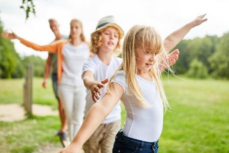 Familie en kinderen oefenen fitness en balans uit op het trimpad