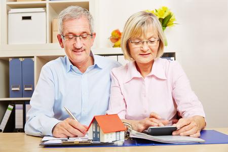 Pareja de ancianos planeando préstamos hipotecarios en un escritorio con casa pequeña