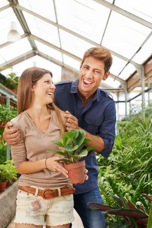Feliz pareja se divierte comprando en el centro de jardinería