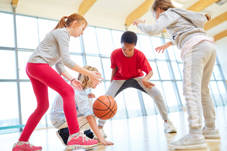 Childrens team plays basketball together in a gym in physical education