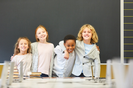 Four cheerful children in multicultural school as friends in front of the empty chalkboard