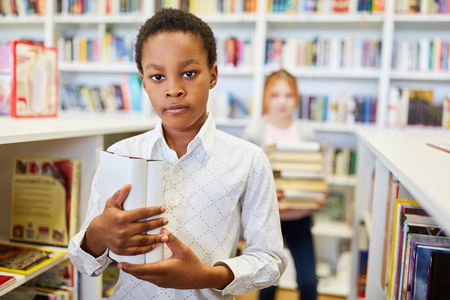 African pupil in the library of the school or a bookstore