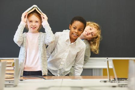 Children have fun in elementary school in class in front of the empty blackboard