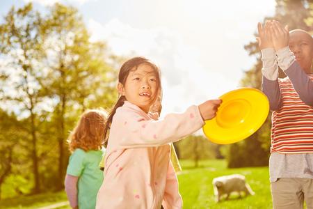 Children in international kindergarten play Frisbee together in the park in summer