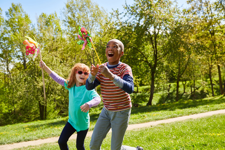 Boy and girl on a meadow with colorful wind wheels celebrates kids birthday Stock Photo