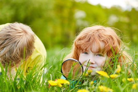 Girl explores the nature and environment with a magnifying glass, lying on a flowers meadow Stock Photo