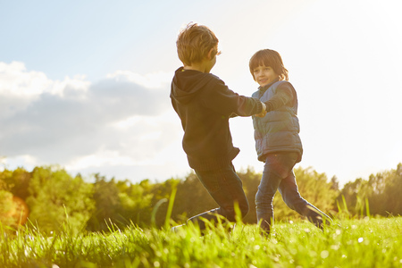 Two children happily dance on a meadow in the sunshine at the children's birthday party