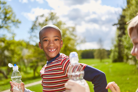African boy smiles naughty and drinks water from a water bottle in the park Stock Photo - 121973593