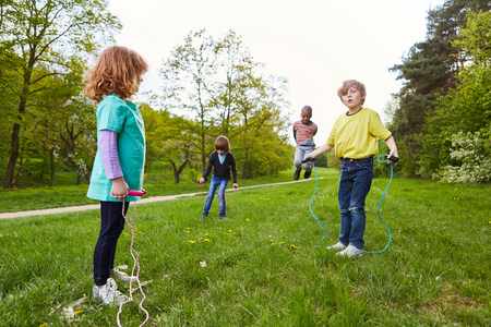 Children group in rope jumping together in the park in summer on a meadow