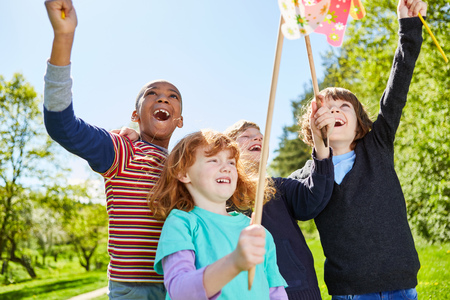 Multicultural kids have fun with colorful windmills on kids birthday