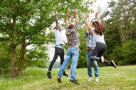 Cheerful young people jump into the air together at the teambuilding workshop