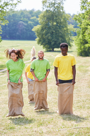 Young people in sack race competition at a teambuilding event