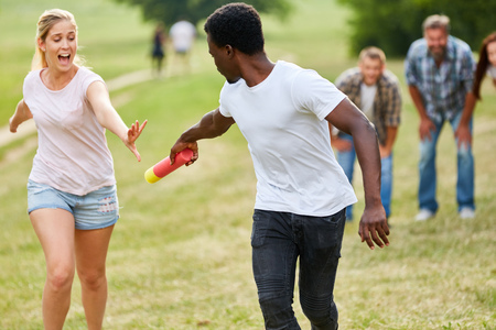Young people in relay race hand the baton on a student sports party