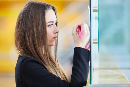 Frau als Passagierin im Flughafenterminal macht sich Notizen oder füllt ein Formular aus