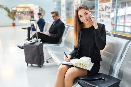 Business woman with appointment calendar is phoning by mobile phone in the airport terminal