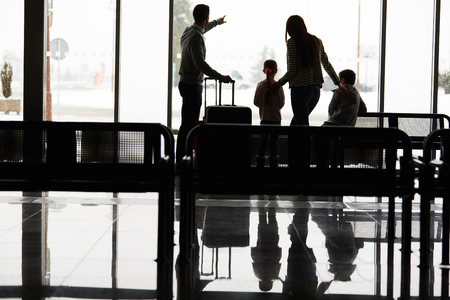 Family and children in the airport terminal wait together for the departure on vacation Stock Photo