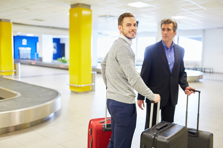 Businessmen on business trip stand with suitcases at baggage claim at airport