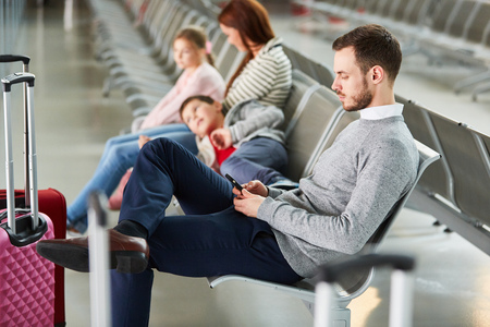 Family with two children on the trip is waiting in the rest area in the airport terminal