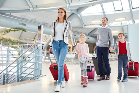 Family with children and luggage on arrival after the flight in the airport terminal
