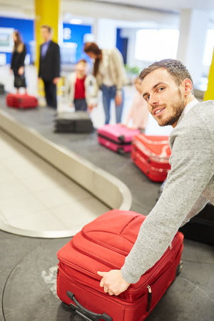 Man as a passenger on the luggage belt picks up his suitcase along with other travelers