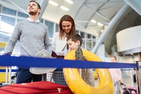 Family and two children with luggage fly into the summer holidays and wait for the flight