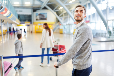 Man as a traveler and his family in the airport terminal on the road on vacation