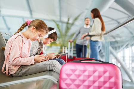 Children play with tablet and smartphone in the waiting time before the flight in the airport 版權商用圖片