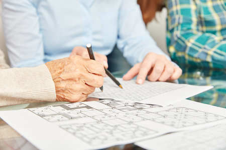 Old woman with wrinkeld hands solves puzzles as a memory training