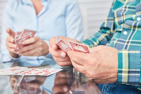 Handen van senioren die kaarten vasthouden tijdens het kaarten in het bejaardentehuis Stockfoto