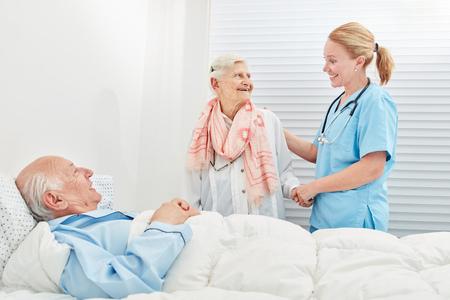 Anciana visita a su marido postrado en cama en el hospital acompañada por un cuidador Foto de archivo