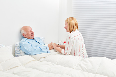 Young woman makes a medical visit to a senior in the hospital Stock Photo