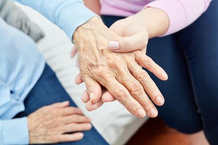 Weibliche Krankenpflegehelferin oder Krankenschwester hält tröstend die Hand einer alten Frau