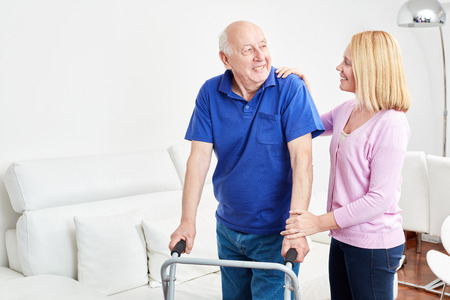 Senior with walker makes rehab for mobility and is supported by therapist