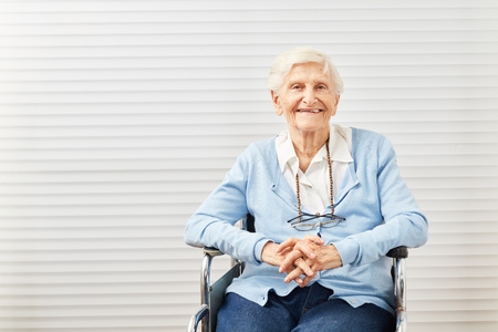 Smiling senior woman is sitting in wheelchair at home or in retirement home