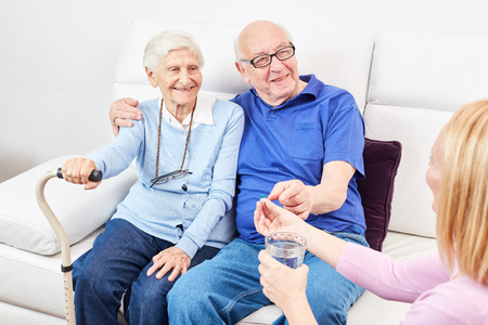 Nursing Woman gives a senior a tablet in the nursing home or at home