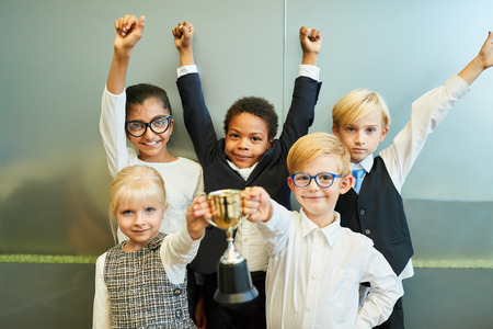 Multicultural children as a business start-up team with a winner's cup of cheering Imagens - 122707913