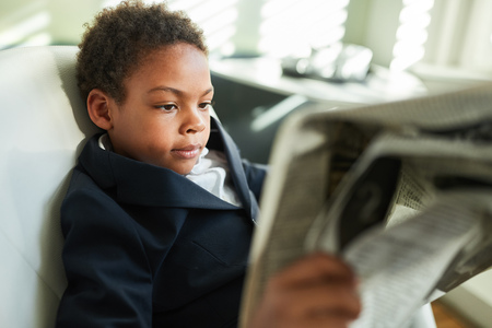 Boy disguised as a manager or consultant reads a daily newspaper in the office