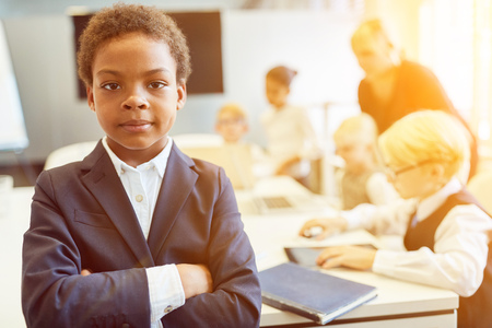 African boy with crossed arms as businessman in front of business team