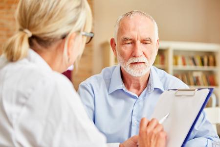 Vrouwelijke arts met klembord interviewt senior man als patiënt in de anamnese Stockfoto