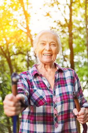 Active senior in nordic walking or hiking in nature in summer 版權商用圖片