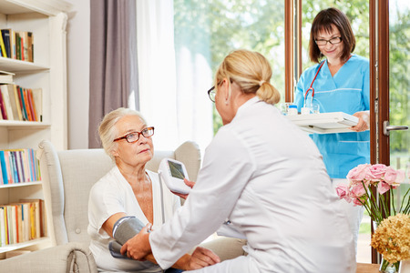 Ärztin misst vorsorglich bei einer Seniorin in ihrem Seniorenheim den Blutdruck