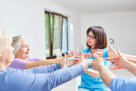 Physiotherapist doing an ergotherapy exercise with elastic band with seniors Zdjęcie Seryjne