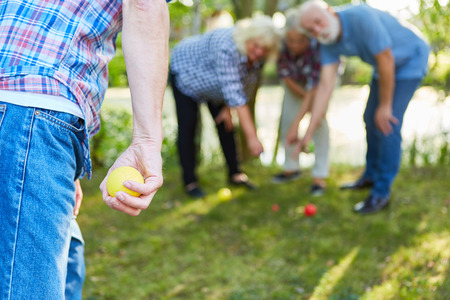 Man is aiming with the ball at the bocce or boules game in the garden with friends Standard-Bild - 122708139