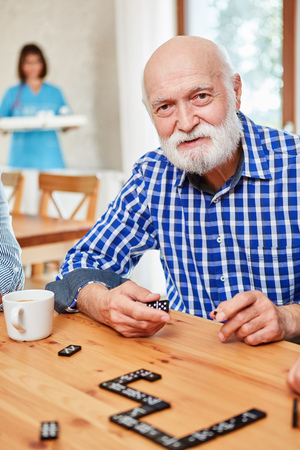 Senior with dementia or Alzheimer's playing in retirement home at domino Stock Photo