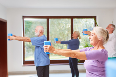 Group of seniors in fitness class during back training for health