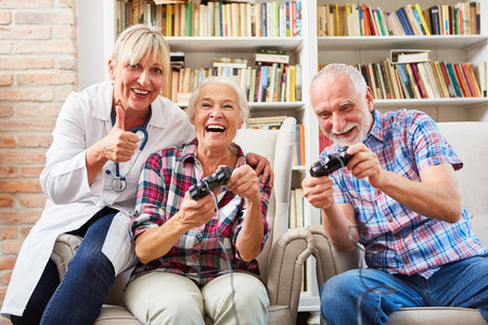 Senior couple and female doctor playing video game at home Stock Photo